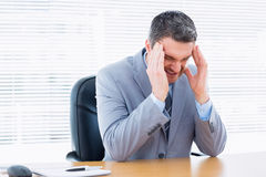 Businessman with severe headache at office desk Stock Image