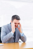 Businessman with severe headache at office desk Royalty Free Stock Photos