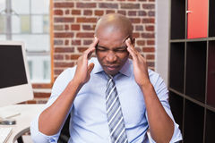 Businessman with severe headache in office Stock Images