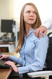 Businessman Sexually Harassing Female Colleague. Businessman Sexually Harasses Female Colleague stock image