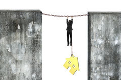 Businessman shackled by gold house hanging on iron chains Stock Photos