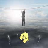 Businessman shackled by gold house hanging on rope Stock Photos