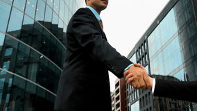 Businessman shake hands. Slow motion. Two businessmen shaking hands with modern glossy building at the background. Middle steadycam shot. Teal and orange style stock video