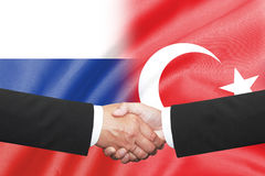 Businessman shakehand over russia and turkey flag. Isolated two businessman shakehand over russia and turkey flag Stock Images