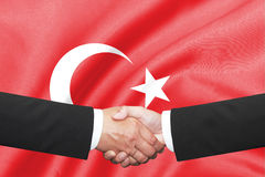 Businessman shakehand over turkey flag. Two businessman shakehand over turkey flag Stock Image