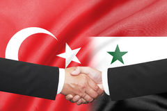 Businessman shakehand over turkey and syria flag. Isolated two businessman shakehand over turkey and syria flag Royalty Free Stock Photos