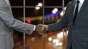 Businessman shakes black man's hand.