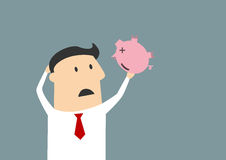 Businessman shaking empty piggy bank Stock Photography