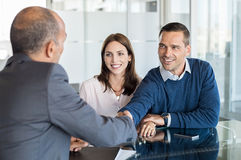 Couple meeting with financial advisor. Businessman shaking hand with a young couple in office. Bank agent and his client shaking hands in conference room. Happy Stock Photos