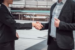 Businessman shaking hands with business woman for demonstrating their agreement to sign contract between their companies. Businessman shaking hands with Royalty Free Stock Image