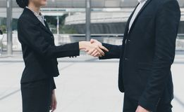 Businessman shaking hands with businesswoman for demonstrating their agreement to sign agreement between their companies. Businessman shaking hands with Stock Images