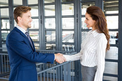 Businessman shaking hands with businesswoman. In office royalty free stock image