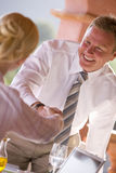 Businessman shaking hands with businesswoman over laptop Royalty Free Stock Images