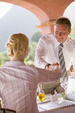 Businessman shaking hands with businesswoman over laptop Royalty Free Stock Photos