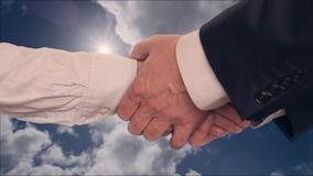 Businessman shaking hands with businesswoman with two hands with cloudy sky on background. Businessman shaking hands with businesswoman with two hands, cloudy stock video footage