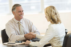 Businessman Shaking Hands With Colleague At Desk royalty free stock images