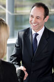Businessman shaking hands with female client or colleague Royalty Free Stock Photography