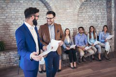 Businessman shaking hands with man besides people waiting for job interview. Businessman shaking hands with men besides people waiting for job interview in a Royalty Free Stock Images