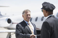 Businessman Shaking Hands With Pilot And Aircraft In Background Royalty Free Stock Image