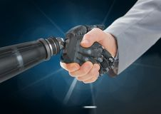 Businessman shaking hands with robot against dark blue background and white light. Close-up of businessman shaking hands with robot against dark blue background stock photos