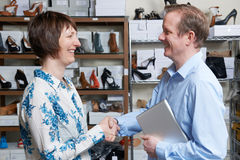 Businessman Shaking Hands With Shoe Store Retailer. Businessman Shakes Hands With Shoe Store Retailer Stock Photos