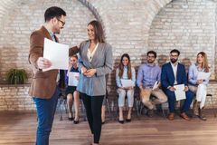 Businessman shaking hands with woman besides people waiting for job interview. Businessman shaking hands with women besides people waiting for job interview in a Stock Images