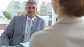 Businessman shaking hands with a woman. In an office stock footage