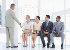 Businessman shaking hands with woman by people waiting for interview Royalty Free Stock Photos