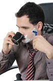 Businessman shaves in the workplace Stock Photography