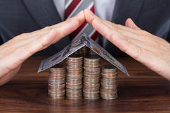 Businessman Sheltering Coins And Banknote In House Shape Royalty Free Stock Images