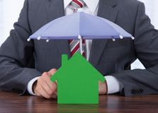 Businessman sheltering house with umbrella. Midsection of businessman sheltering house with umbrella at desk Royalty Free Stock Images