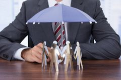 Businessman sheltering paper people with umbrella. Midsection of businessman sheltering paper people with umbrella at desk Stock Images