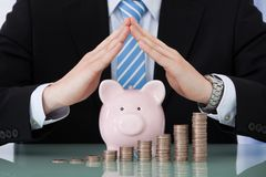 Businessman sheltering piggybank and coin stacks Stock Photography