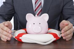 Businessman sheltering piggybank with lifebelt at desk Royalty Free Stock Image
