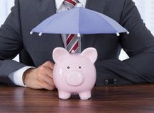 Businessman sheltering piggybank with umbrella at desk Stock Images