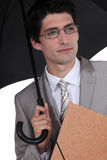 Businessman sheltering from rain Royalty Free Stock Photography