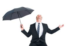 Businessman sheltering under black umbrella testing Royalty Free Stock Photography