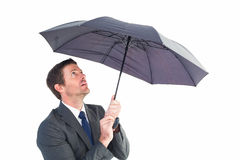 Businessman sheltering under black umbrella Royalty Free Stock Images