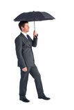 Businessman sheltering under black umbrella Stock Photos