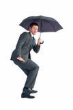 Businessman sheltering under black umbrella Stock Photo