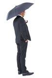 Businessman sheltering under black umbrella Royalty Free Stock Photography