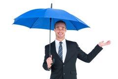 Businessman sheltering under black umbrella Stock Photography