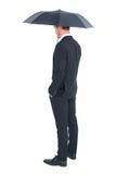 Businessman sheltering under black umbrella Royalty Free Stock Photos