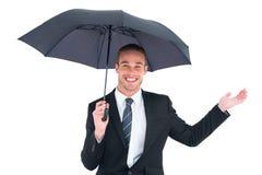 Businessman sheltering under black umbrella Stock Image