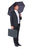 Businessman sheltering under bllack umbrella Stock Photography