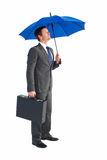 Businessman sheltering under blue umbrella Royalty Free Stock Image