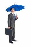 Businessman sheltering under blue umbrella Royalty Free Stock Image