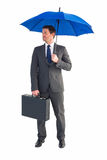 Businessman sheltering under blue umbrella Stock Photo