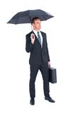 Businessman sheltering under umbrella holding briefcase Stock Photos