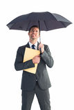 Businessman sheltering under umbrella holding file Royalty Free Stock Photography